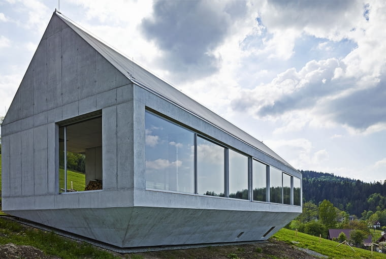 """Dom Arka, Brenna, Polska, proj. Robert Konieczny KWK Promes, nominacja w kategorii budynki zrealizowane, domy jednorodzinne. Dom własny architekta to budynek mocno nietypowy jak na polskie warunki - prosta, oszczędna w całości wykonana z betonu, który jest także materiałem wykończeniowym. Betonowy jest także dach, a właściwie dwa dachy, bo budynek unosi się nad stokiem a przestrzeń pomiędzy budynkiem a powierzchnią terenu to forma wyglądająca jak odwrócony do góry nogami dach. Więcej o tym budynku przeczytasz <a href=http://www.bryla.pl/bryla/1,85301,14268315,Betonowa_arka_Roberta_Koniecznego_gotowa.html><span style=""""color: #c0c0c0;"""">TUTAJ</span></a>"""