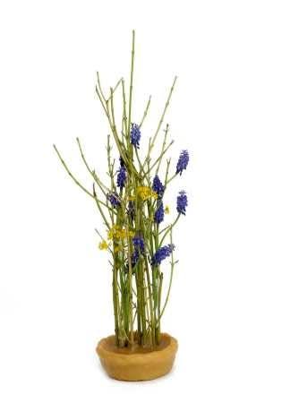 W stygnącej stearynie dobrze będą się trzymać ułożone równolegle pędy derenia. W dowiązanych do nich próbówkach ułożono szafirki i kwiatostany smagliczki.