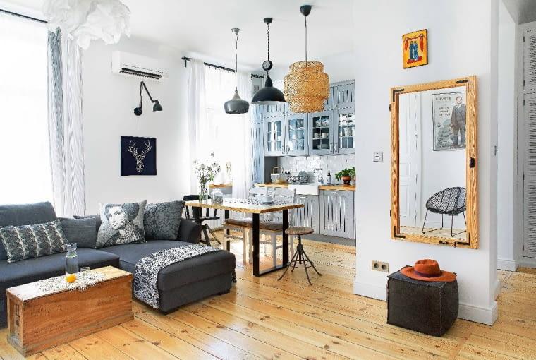 PRZY KANAPIE (Livingroom Concept Store) stoi stół wykonany przez tatę Kamili oraz stołek zodzysku. Lustro - podobnie jak to w łazience - oprawiono w ramę po starym oknie. Poduszka z wizerunkiem damy jest z IKEA.