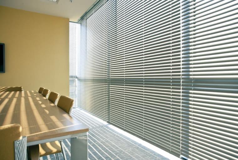 Klasyczne, aluminiowe żaluzje wciąż niepodzielnie królują w oknach biurowych.