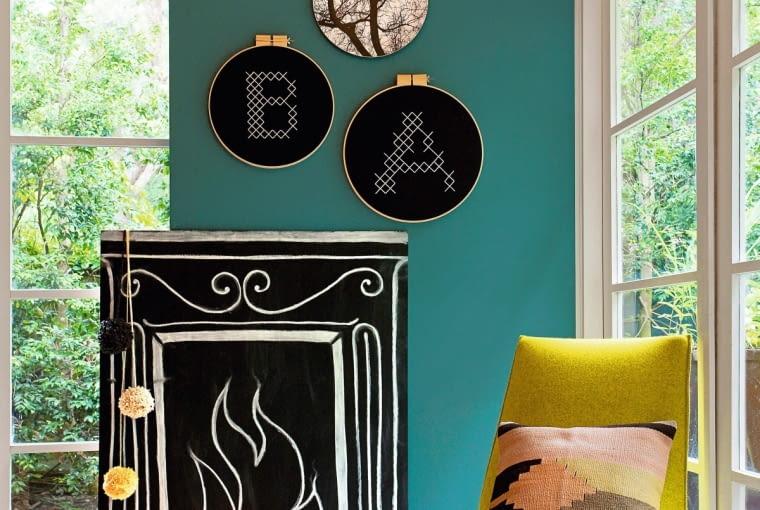 Farbą tablicową możesz namalować to, czego ci brakuje w domu. Choćby kominek... Przed nim postaw kilka świec lub połóż sznur lampek. Taka aranżacja zaskoczy gości.