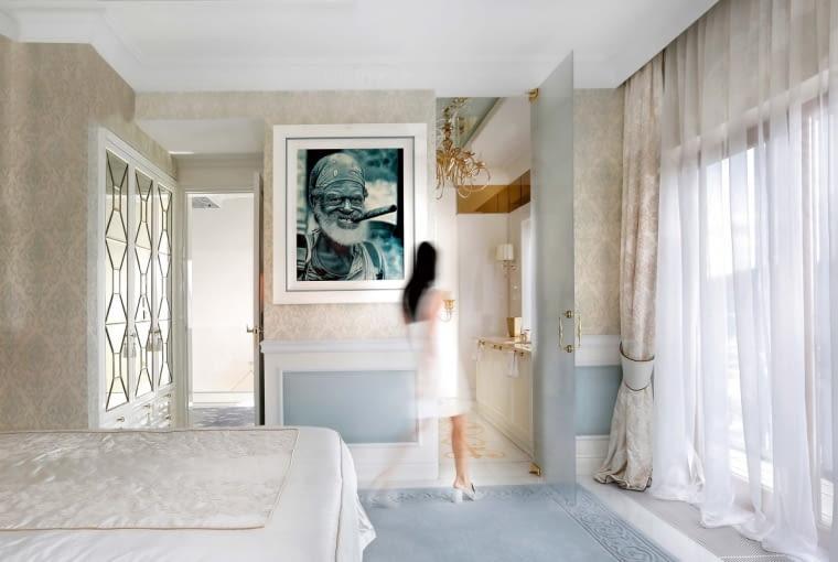 Zsypialni gospodarzy można przejść bezpośrednio do łazienki rozświetlonej złotymi akcentami, które harmonizują zpastelową paletą. Biel znalazła tu piękne dopełnienie wbladym błękicie. Zdjęcie sędziwego brodacza przyjechało zwakacji na Kubie.