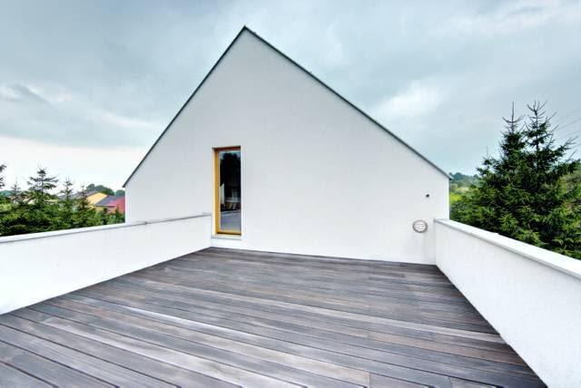 Drewniany taras nad wiatą garażową, na który można wyjść z głównej sypialni