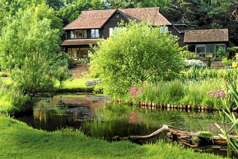 Wild garden in Sussex with natural pond, logs, willows and marginal planting SLOWA KLUCZOWE: wild house marginal willow mown logs pond garden