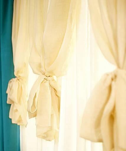DEKORACJE OKIEN - FINEZYJNE UPIĘCIE. Dolne brzegi zewnętrznej warstwy firan (sięgającej do połowy okna) przewiązano opaskami uszytymi z tej samej tkaniny.