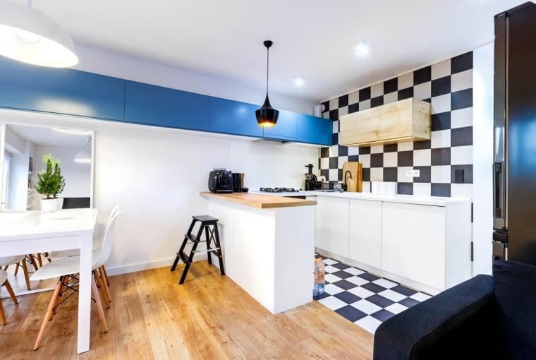 Elementem spajającym kuchnię z pozostałą częścią pomieszczenia jest ciąg szafek biegnących wysoko wzdłuż ściany.