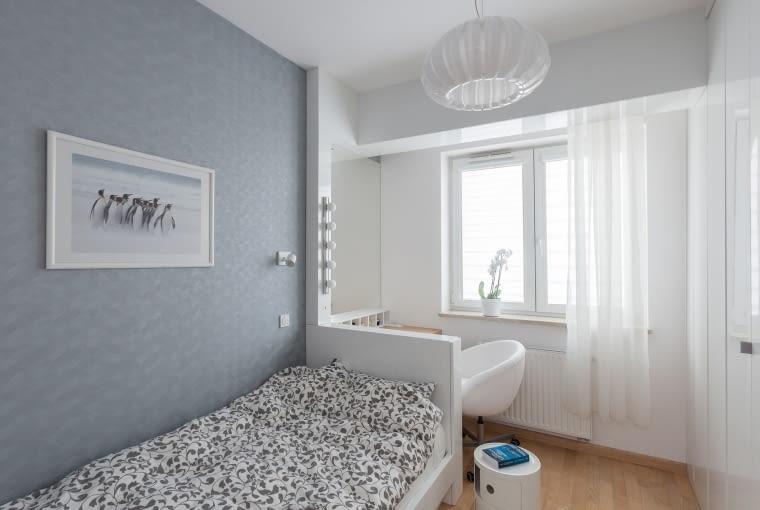 W sypialni za łóżkiem znajduję się toaletkę z lustrem, oświetleniem i miejscem na drobne rzeczy. Zabudowa stolarska toaletki połączona jest z zabudową belki konstrukcyjnej budynku, za którą schowano mocowanie zasłonek.