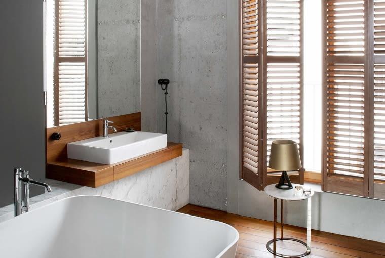 Surowy klimat łazienki ocieplają drewniane shuttersy, łagodnie filtrujące światło i teakowa wodoszczelna podłoga, wykonana techniką jachtową (deski łączone czarną gumą). Wanna Balia (Marmorin), umywalka Vero (Catalano), armatura Pan (Zucchetti).