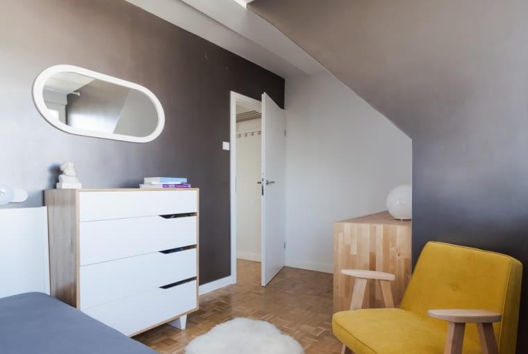 Sypialnia jest urządzona w ciepłych szarościach