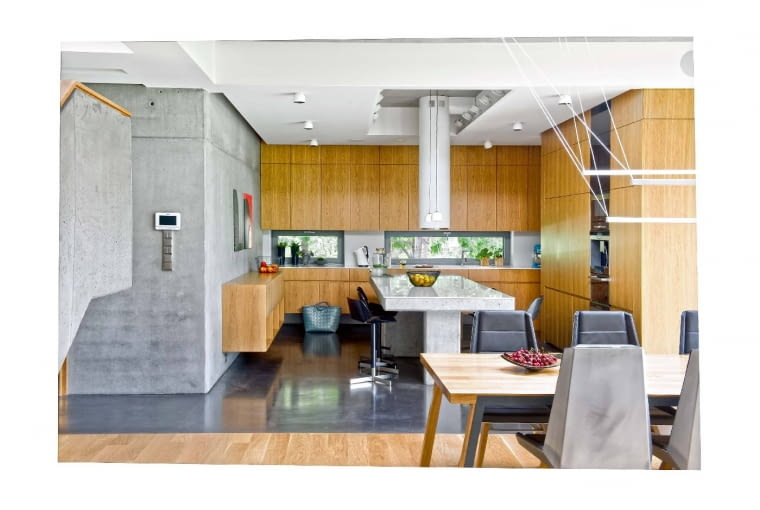 Poziome ciągi zabudowy kuchennej w dębowym fornirze porządkują wnętrze. Okna przeszły metamorfozę; klasyczne duże otwory okienne zastąpiono 'szklaną taśmą', kierującą światło na blat roboczy.