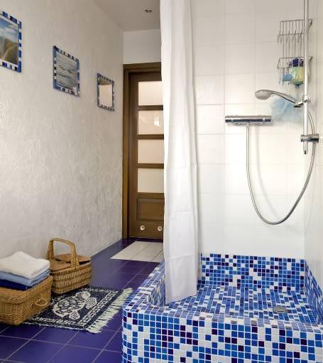 MIESZKANIE. Źródłem inspiracji podczas urządzania łazienki były - jak na podróżników przystało - wyspy greckie. Stąd biel i błękit, niewygładzony tynk na ścia-nach oraz szklana mozaika w różnych odcieniach niebieskiego. Wiklinowe koszyki służą jako minischowki.