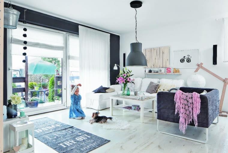 OD WIOSNY DO JESIENI. Naturalnym przedłużeniem salonu jest ogródek - wystarczy rozsunąć tarasowe drzwi. Stolik kawowy z IKEA nabrał szyku, gdy właściciele zamontowali na nim drewniany blat. Na podłodze leżą deski z bielonego dębu (Kronopol).