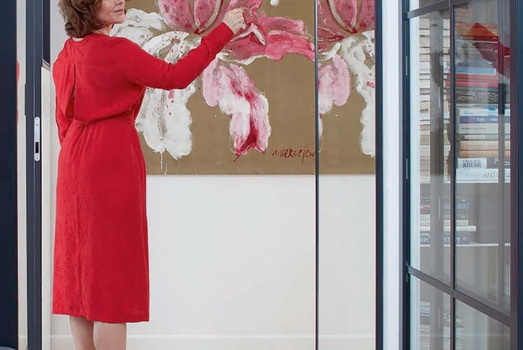 BALONIK, czyli lampa-kinkiet z ręcznie formowanego szkła (marki Brokis), intrygująco prezentuje się w holu. W głębi fragment obrazu Anki Mierzejewskiej 'Orchidea' (akryl na aksamicie).