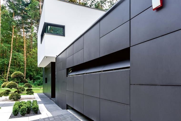 Brama ukryta w elewacji. Konstrukcja tej bramy garażowej dostarczana jest przez producenta jako rozwiązanie standardowe i ogólnodostępne. Dopiero jej wykończenie jest indywidualne i inne dla każdej inwestycji. Można na nią położyć dowolny materiał. Fantazję ogranicza jedynie ciężar stosowanej okładziny, co oznacza, że bramę możemy wykończyć praktycznie wszystkim, poza kamieniem i betonem. W prezentowanym domu na bramie zastosowano te same płyty, co na elewacji. Segmentowa brama dzięki temu, że jest ocieplana i szczelna po obwodzie, zapewnia także budynkowi wysoką energooszczędność.