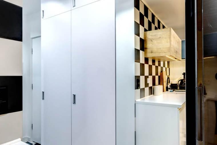 Lustro na całą wysokość ściany jest także u wejścia do kuchni. Ma ono sprawiać, żeby mieszkanie wydawało się większe.