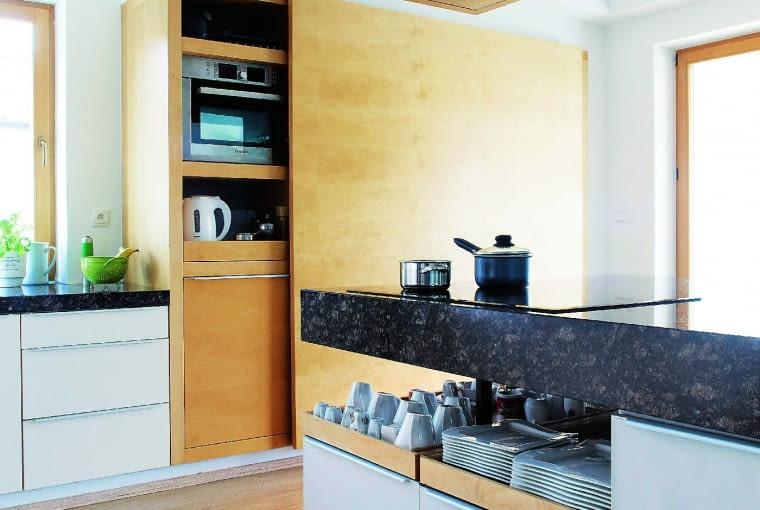 POD RĘKĄ. Na niskich szafkach pod grubym granitowym blatem znajdują się wysuwane tace - dobre miejsce na używane na co dzień naczynia.