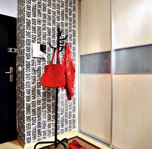 Od drzwi gości wita tapeta w literkowy wzór pokrywająca ścianę na wprost wejścia. Na podłodze w przedpokoju - bambusowy dywanik.