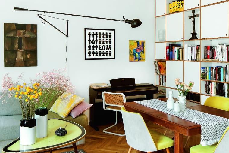Żyrandol z lat 70., nawiązuje formą do stylu Bauhaus. Właściciel traktuje go jak funkcjonalną, ażurową rzeźbę. Po prawej barwny obraz Piotra Dudka. Wazony czarno-białe Normann Copenhagen (Fabryka Form). Lampa ścienna Flos 265.