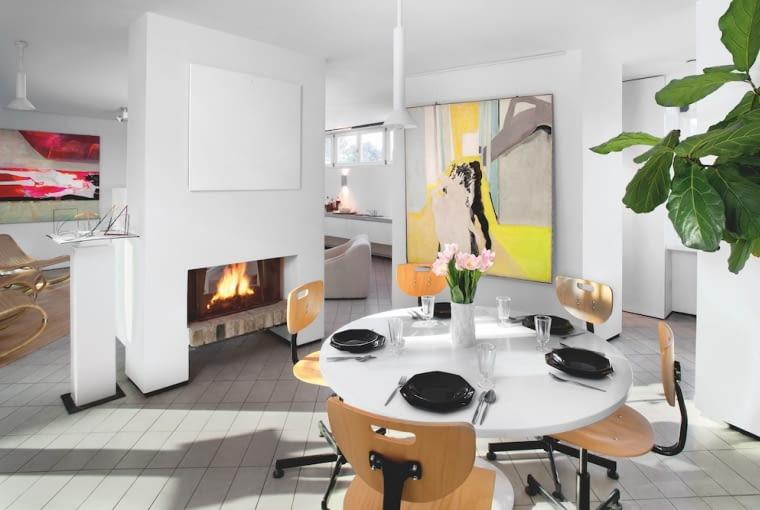 Prosty kominek od strony kuchni ma ukrytą szafkę na wielkie półmiski. Okrągły stół na metalowej nodze to projekt Krystyny z lat 70. Wokół przemysłowe, regulowane krzesła.
