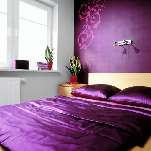 W sypialni gospodarze odpoczywają od liter - tutaj pomalowaną na ciemny fiolet ścianę zdobi arabeska (wzór z szablonu).