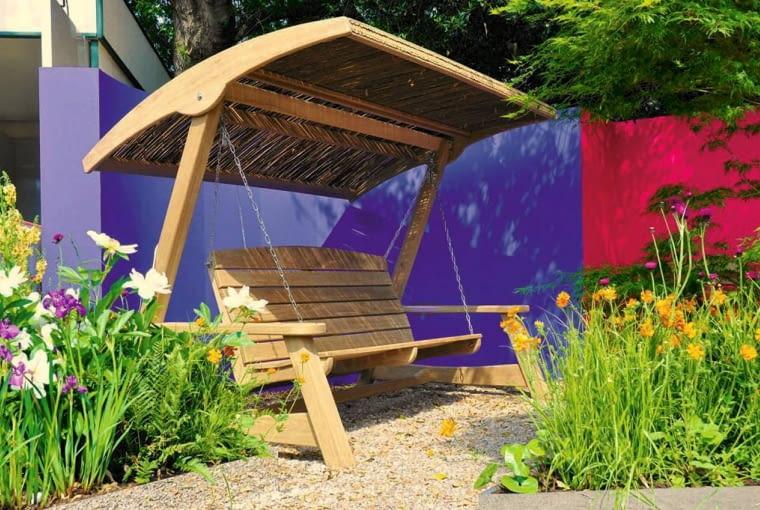 Ten ogrodowy kącik zaskakuje odważną kolorystyką ścianki osłaniającej przed wiatrem, zapewniającej kameralność.
