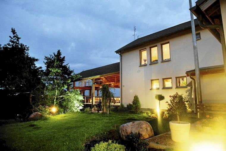 Dom na skarpie. Widok na dom, taras i okolicę od strony ogrodu przy sypialni. To miejsce, osłonięte murami budynku i wysokimi drzewami, sprzyja wypoczynkowi