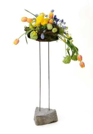 Z takiej konstrukcji kwiaty spływają kaskadą. Na szczycie dwóch prętów umocowano grubą korę, na której ułożono w gąbce tulipany, hortensję, niebieskie kwiatostany prusznika (Ceanothus), jaskry, żółtą smagliczkę skalną i owoce trojeści.