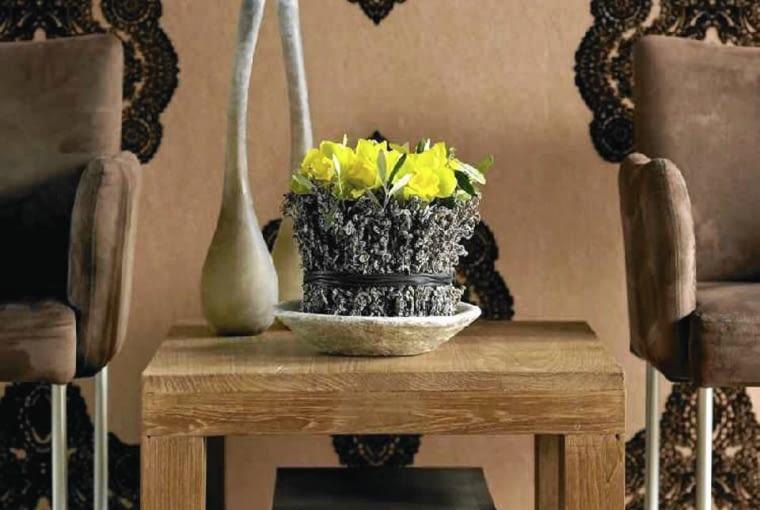 Żółte cymbidia w pojemniku otoczonym suszonymi gałązkami paproci i żywymi z oliwki.
