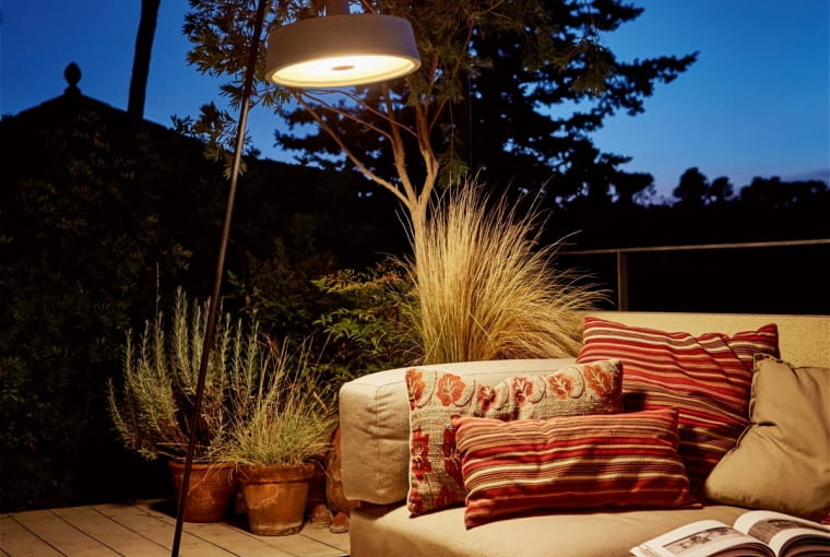 Jak w salonie. Stoi tu kanapa wymoszczona poduszkami i lampa podłogowa w modnym stylu industrialnym. Ale ścianę tworzy las, a sufitem jest niebo. Lampa zaś odznacza się pełną wodoszczelnością i może bezpiecznie być umieszczana na zewnątrz. Wykonana z polietylenu, daje łagodne, rozproszone światło. Soho, Marset, marset.com