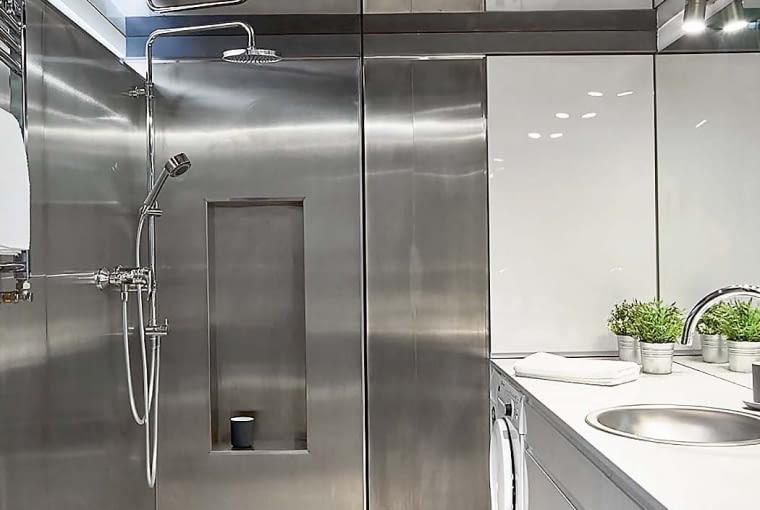 W kabinie prysznicowej typu walk-in (bez szczelnie zamykanych drzwi) nie ma brodzika. Zastąpiono go odpowiednio wyprofilowaną podłogą, w której zamontowano odpływ liniowy. Oprócz rączki prysznicowej w kabinie zainstalowano deszczownicę - idealną do szybkiego odświeżenia się i relaksu w strugach wody. Mała wnęka-półka to wygodne miejsce na kąpielowe akcesoria.