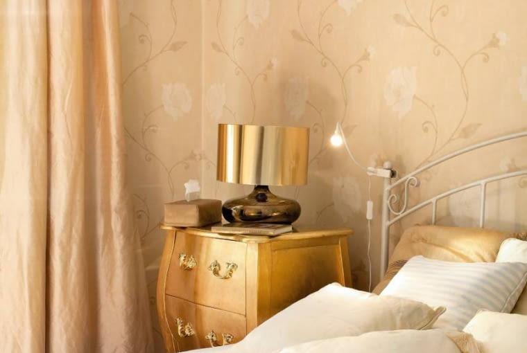 Lampa ze złotym kloszem emituje nastrojowe światło. Dowieczornej lektury służy lampka ledowa przymocowana klipsem do wezgłowia łóżka.