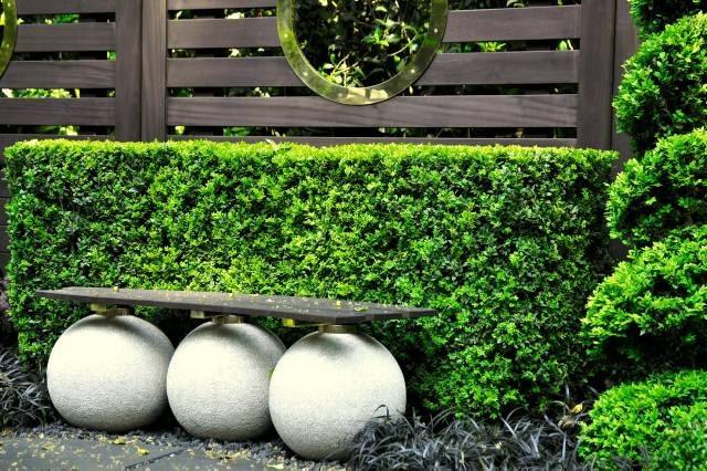 Oryginalna ławka z siedziskiem wspartym na betonowych kulach nada ogrodowi charakterystyczny rys