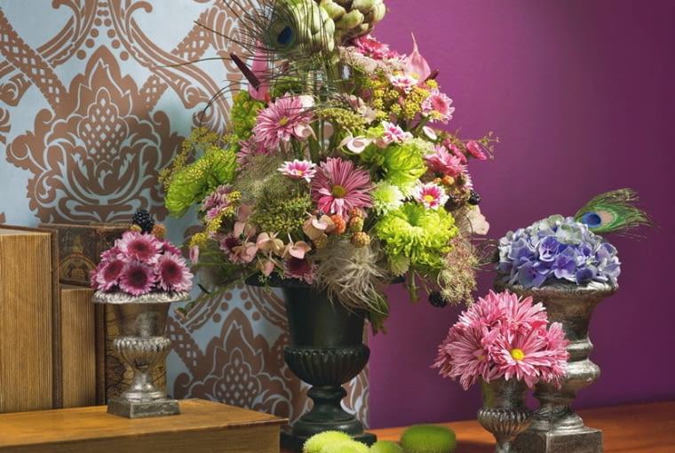 Orientalne kompozycje kwiatowe. Mocną sylwetkę karczocha równoważą delikatne owocostany powojników, baldachy kopru i pawie pióra