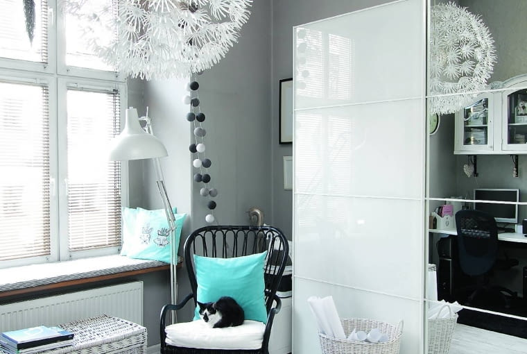 Szeroki parapet służy czasem jako legowisko dla kotów, które - jak widać - i tak wolą fotele. Wiklinowy kosz na papiery kupiono wsklepie Inne Meble.