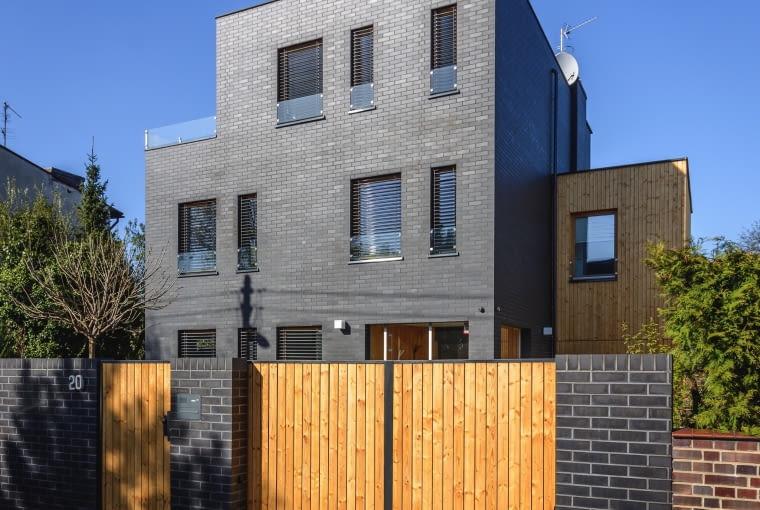 Układ otworów na elewacji tworzy piękną wertykalną kompozycję. Okna wyższych kondygnacji mają niski parapet (około 50 cm), co stwarza ciekawą perspektywę od strony patrzącego z wnętrza domu. Dla bezpieczeństwa domowników w dolnych partiach okien pojawiły się szklane balustrady, stanowiąc dodatkowy element dekoracyjny.