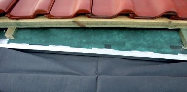 Krok 4. Następnie wykonuje się nacięcia w kontrłatach nad oknem i montuje w nich ukośnie rynienkę odwadniającą. Pod nią powinna się znaleźć górna część izolacji przeciwwilgociowej. Po zakończonym montażu rynienka będzie niewidoczna.
