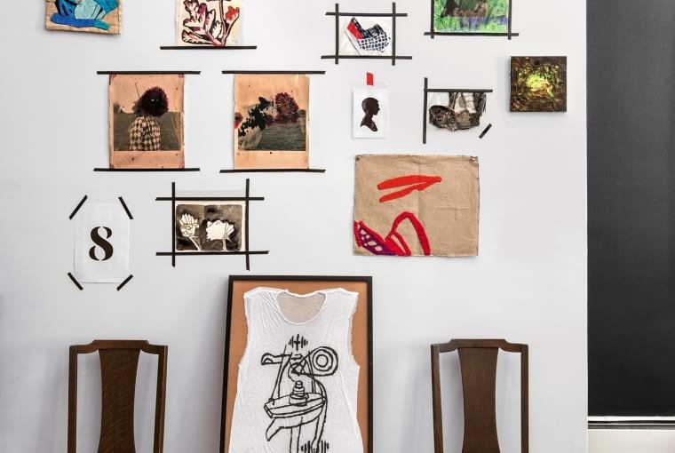 Minigaleria w sypialni - nad zabytkowymi dębowymi krzesłami wiszą kolaże Karen Gilardi i zdjęcia Dietmara Busse. W charakterze stelaża kultowy stołek Tolix Chantal Andriot.