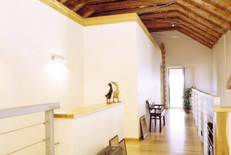 Nad stropami pomieszczeń na piętrze, pod odsłoniętą więźbą dachową, powstały schowki