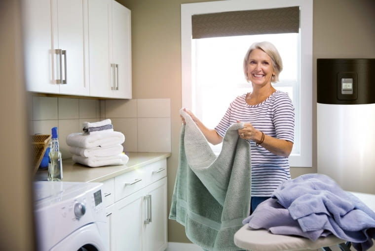 -Smiling woman folding laundry in laundry room