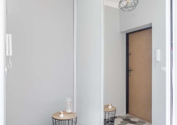 W odróżnieniu od sypialni i salonu z kuchnią - wejście do mieszkania jest bardzo stonowane i minimalistyczne. Aranżację wzbogacono w geometryczny patchwork podłogowych kafli.