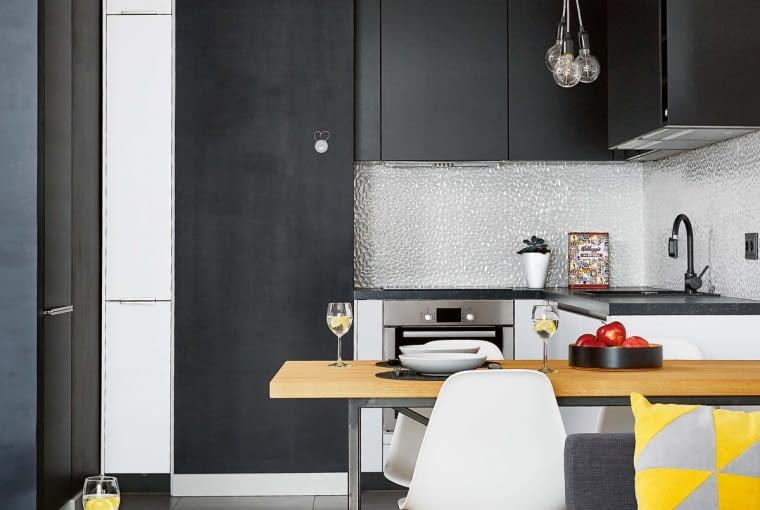 Ścianę nad blatem chronią płytki 3D firmy Max-Fliz. Kafelki imitujące perłową mozaikę efektownie odbijają światło. UMOWNĄ GRANICĘ między kuchnią (6,5 m kw) a pokojem dziennym wyznacza stół z drewnianym blatem na stalowym stelażu (mebel zrobiono na zamówienie). Towarzyszą mu nowoczesne krzesła o lekkiej formie, inspirowane projektami Charlesa i Ray Eamesów.