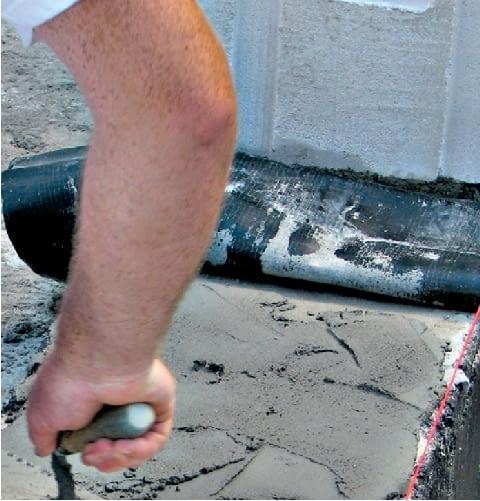 Krok 2. Folię rozkłada się na warstwie zaprawy cementowej, która wyrównuje górną powierzchnię ścian fundamentowych