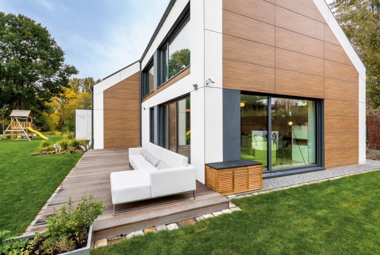 Elewacja domu została wykonana z nowoczesnych płyt elewacyjnych w harmonijnie dobranych odcieniach brązu, bieli i szarości