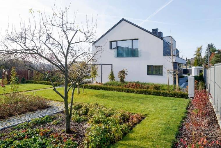 Na tyłach domu rozciąga się ogrodowa część działki, otoczona ażurowym ogrodzeniem, wykonanym z metalowej siatki