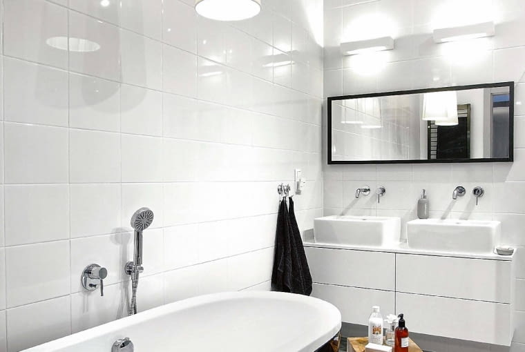 Dwa źródła światła nad wanną wystarczająco rozjaśnią nie tylko miejsce do kąpieli, ale również znaczną część łazienki. W wysokiej łazience można sobie pozwolić na lampy wiszące.