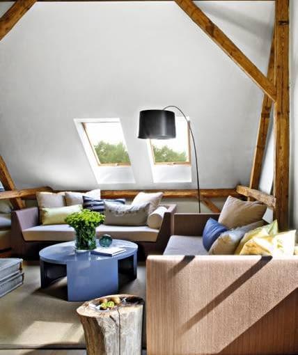 Salon na poddaszu. O uroku wnętrza w dużym stopniu decyduje odsłonięta drewniana konstrukcja dachu