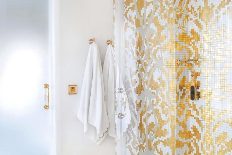 Ścianę natrysku wyłożono złoto-białą mozaiką Sicis. Złoty odcień mają też wieszaki, uchwyty i włączniki. Ornament na szklanej ścianie prysznica to kolejny projekt Katarzyny Sybilskiej.