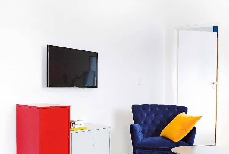 Telewizor zamontowany na ścianie przypomina obraz. Czarny ekran wraz z prostokątnymi szafkami tworzy kolorową geometryczną kompozycję, przywodzącą na myśl projekty grupy De Stijl oraz malarstwo Pieta Mondriana. Wiekowy fotel ma nowe obicie zrobione z... zasłony. Aksamitną tkaninę projektantka znalazła w sklepie z tanią odzieżą. Odświeżyła ją i wykorzystała do odnowienia mebla.