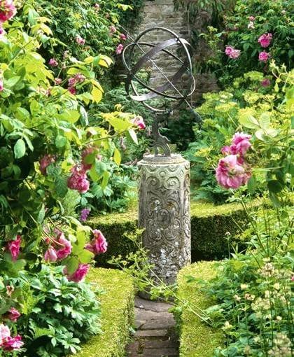 Sundial amidst old roses in parterre garden - Alderley Garden, Glos