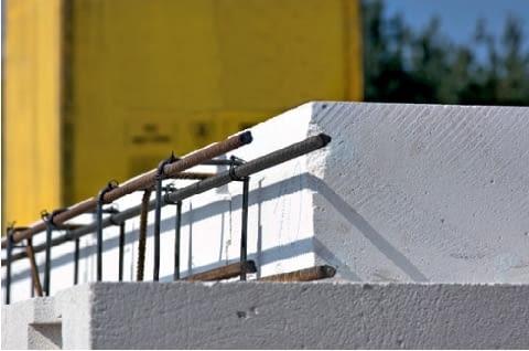 Układanie wieńca na ścianach jednowarstwowych z betonu komórkowego. Po ułożeniu elementów stropu (tu płyt prefabrykowanych), na ścianach zewnętrznych umieszcza się - zgodnie z projektem stropu - zbrojenie wieńca
